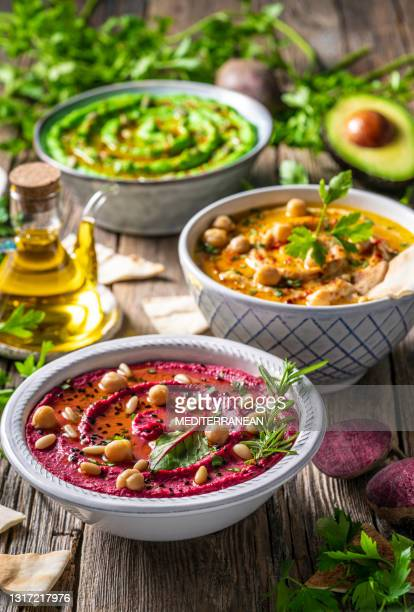 hummus three bowl of chickpeas, avocado and beetroot vegetables for dip on rustic wooden table - lebanon country stock pictures, royalty-free photos & images