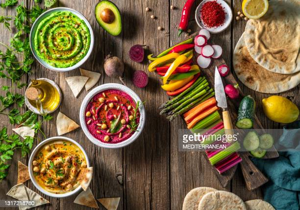 hummus three bowl of chickpeas, avocado and beetroot with cut vegetables for dip on rustic wood table - lebanon country stock pictures, royalty-free photos & images