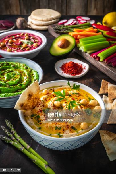 hummus three bowl of chickpeas, avocado and beetroot with cut vegetables for dip on dark wood - lebanon country stock pictures, royalty-free photos & images