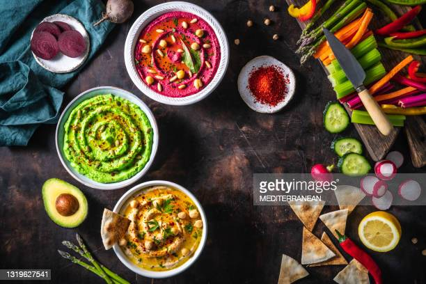 hummus three bowl of chickpeas, avocado and beetroot with cut vegetables sticks on dark wood table - lebanon country stock pictures, royalty-free photos & images