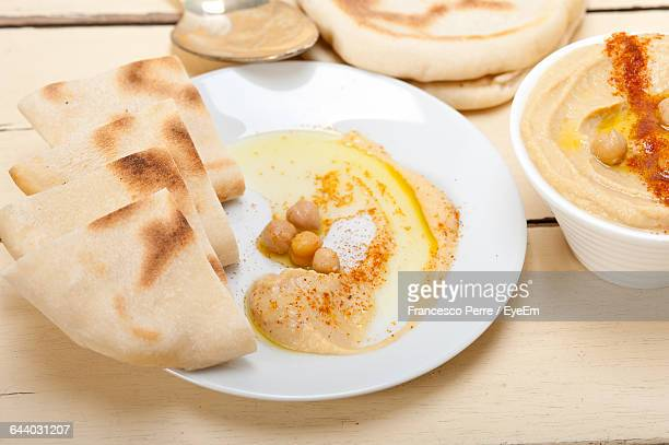 Hummus With Pita Bread Served On Table