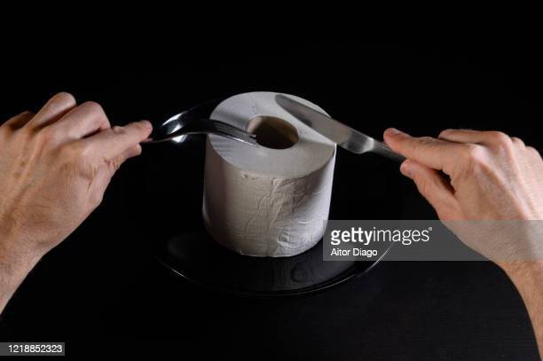 humor. close up of man's hands cutting a roll of toilet paper. - emorroidi foto e immagini stock