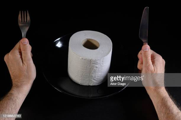 humor. close up of man's hands with fork and knife ready to eat a roll of toilet paper. - hemorroide fotografías e imágenes de stock