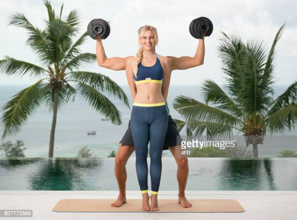 humor, personal trainer hiding with dumbells, fitness coach motivating his client on vacation - freaky couples stock photos and pictures