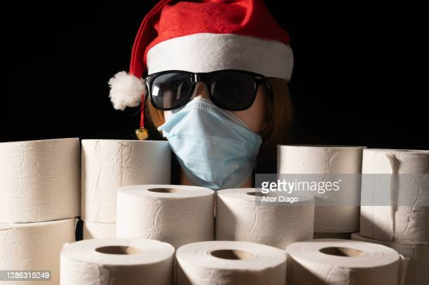 humor: woman face representing santa claus with protection mask and sun glasses surrounded of toilet papers roles. black background. - black mask disguise stock pictures, royalty-free photos & images