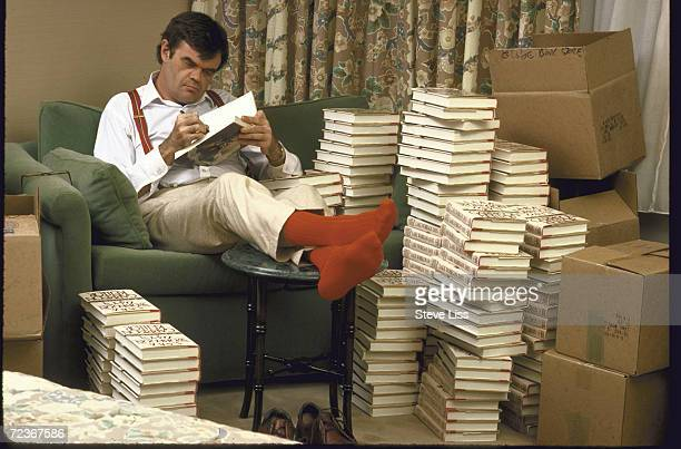 Humorist Garrison Keillor autographing large stacks of his book Lake Wobegone Days in his hotel room