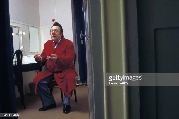 Humoriste Raymond Devos dans sa loge jonglant avec des nez de clown, circa 1980 en France.