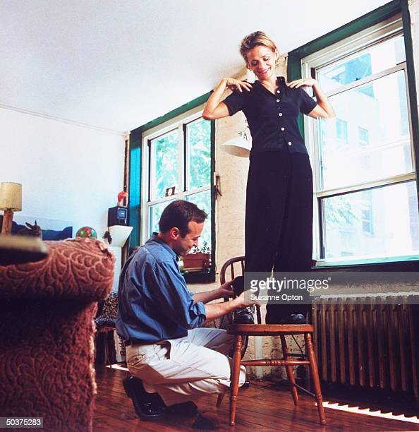 Humorist/writer David Sedaris adjusting the hem on pants of his sister Amy while she stands on chair at his apt