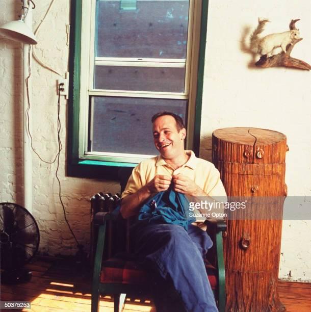 Humorist/writer David Sedaris mending his pajamas at home