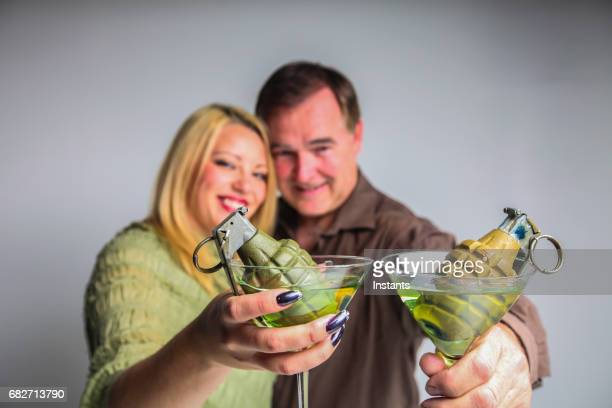 humorous concept of an explosive relationship, may it be a couple or business, where a man and a woman are holding martinis, with each a grenade in their glass. - molotov cocktail stock pictures, royalty-free photos & images