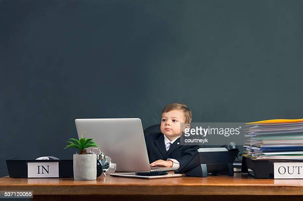 humorous image of young boy working on a laptop computer - outbox filing tray stock pictures, royalty-free photos & images