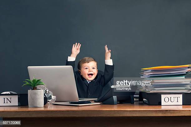 humorous image of young boy working on a laptop computer - finishing stock pictures, royalty-free photos & images