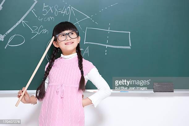 Humorous little girl playing teacher in classroom