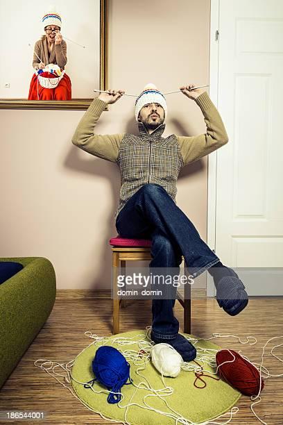 Humorvolle, Mann sitzt auf einem Stuhl und Stricken winter Mütze, Innenansicht