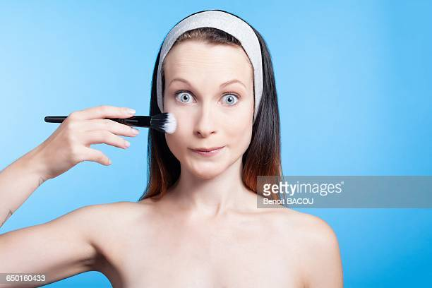 Humorous portrait of a woman using a makeup brush on face