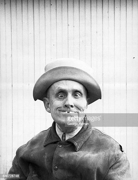 Humorous portrait of man crossing eyes and exposing missing teeth Undated photograph