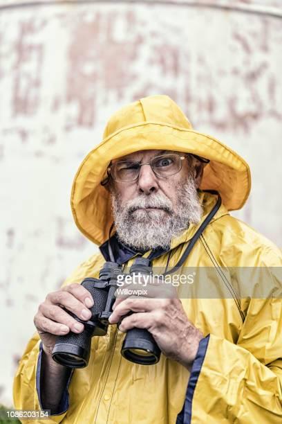 jumelles de holding capitaine humoristique looking at camera - pluie humour photos et images de collection