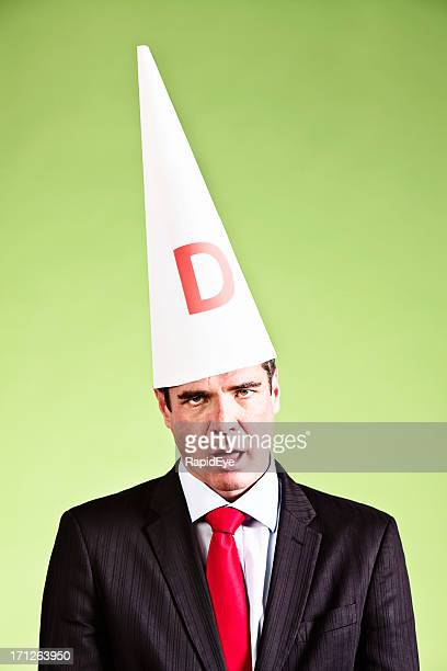 humorous study of businessman looking dumb in dunce cap - dunce's hat stock pictures, royalty-free photos & images