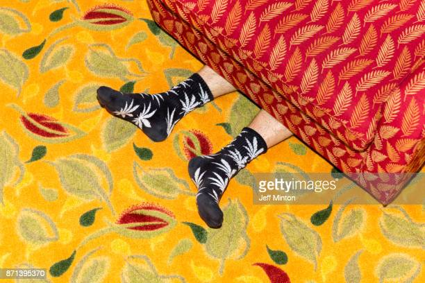 Humorous view of a persons feet sticking out from under a brightly colored and pattered sofa while laying on a brightly colored leaf print rug