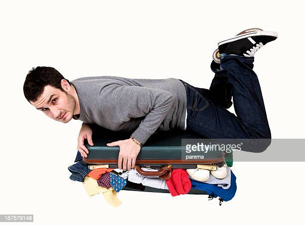 Humorous view of man trying to close an overpacked suitcase