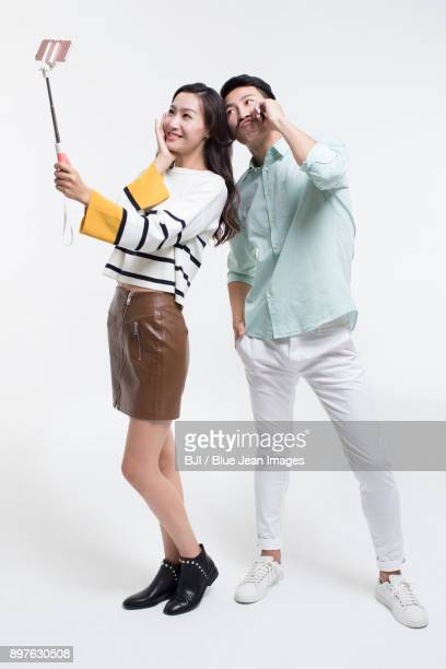 Humorous young couple taking self portrait with smart phone