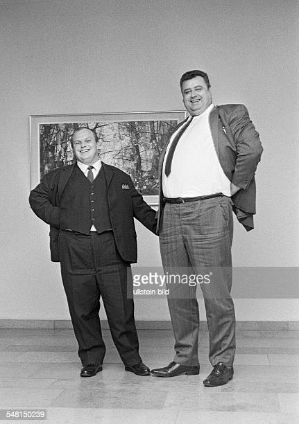 humour people contrast a runtish man and a largesized man stand side by side dwarf and giant aged 30 to 40 years