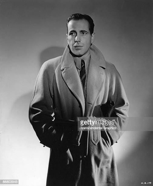 Humphrey Bogart dons a trench coat during a publicity shoot in Hollywood around 1940.