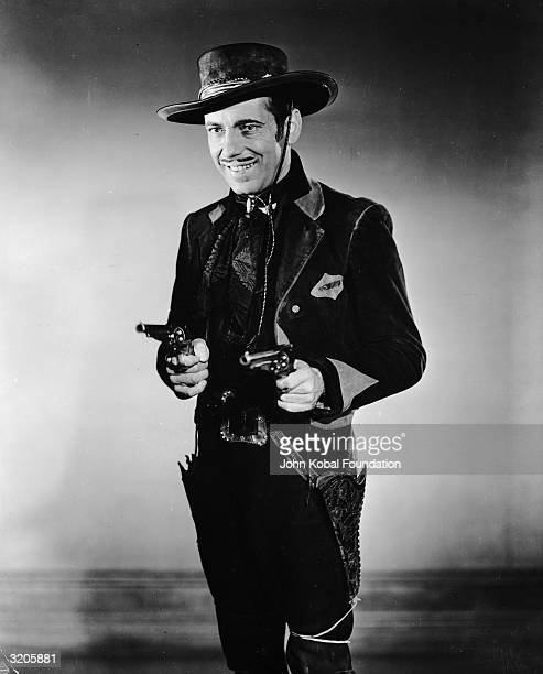 Humphrey Bogart draws his pistols while playing the role of Whip McCord in the film 'The Oklahoma Kid'