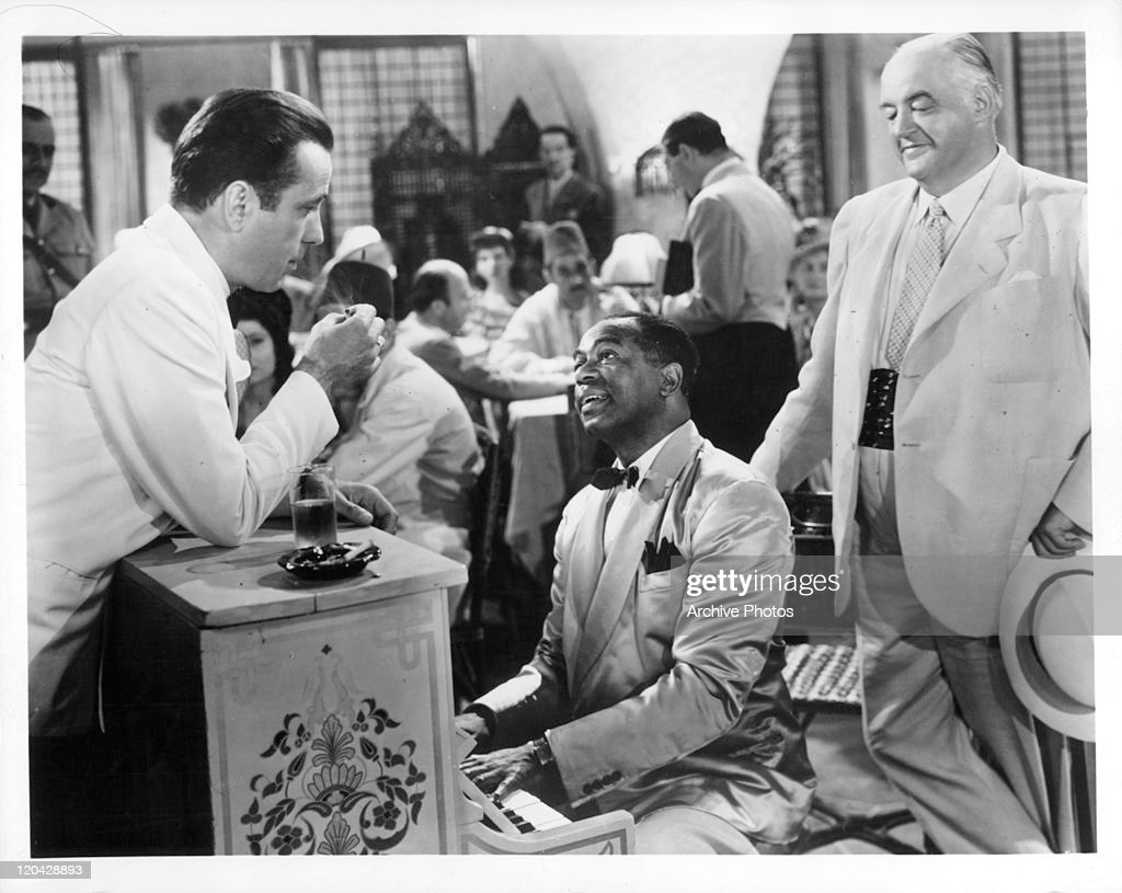 Humphrey Bogart leans on piano Dooley Wilson is playing in a scene from the film 'Casablanca', 1942.
