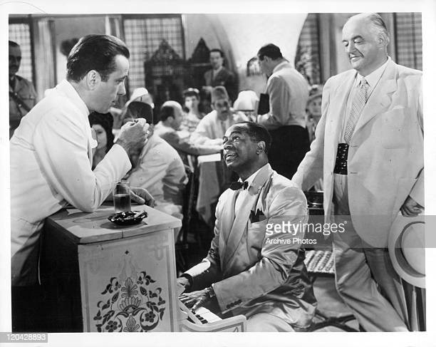Humphrey Bogart leans on piano Dooley Wilson is playing in a scene from the film 'Casablanca' 1942