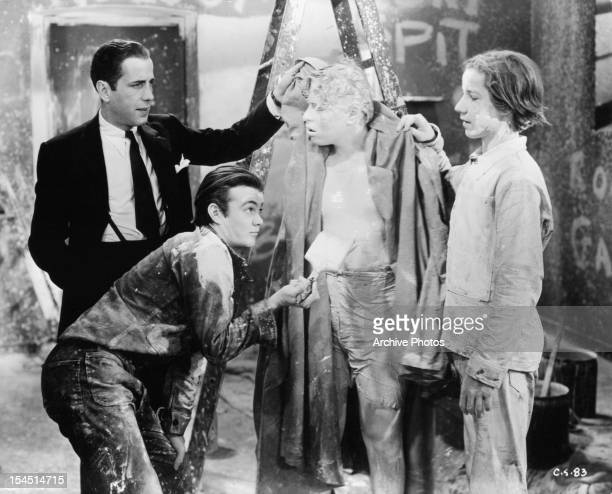 Humphrey Bogart watches as Leo Gorcey paints Billy Halop in a scene from the film 'Crime School' 1938