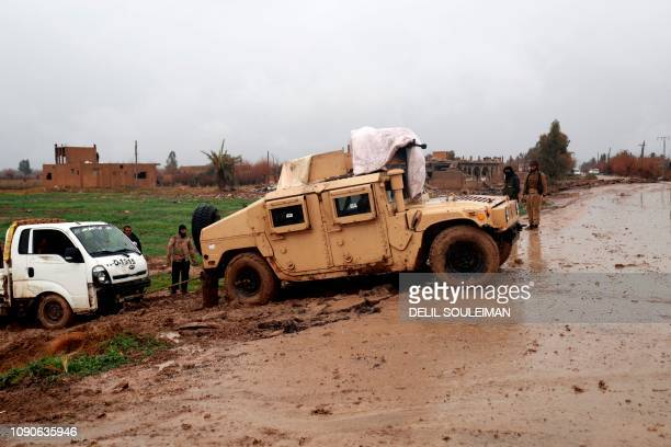 A Humvee belonging to the SDF helps tow a pickup truck on January 28 in the town of Sousa in Syria's eastern province of Deir Ezzor Kurdishled...