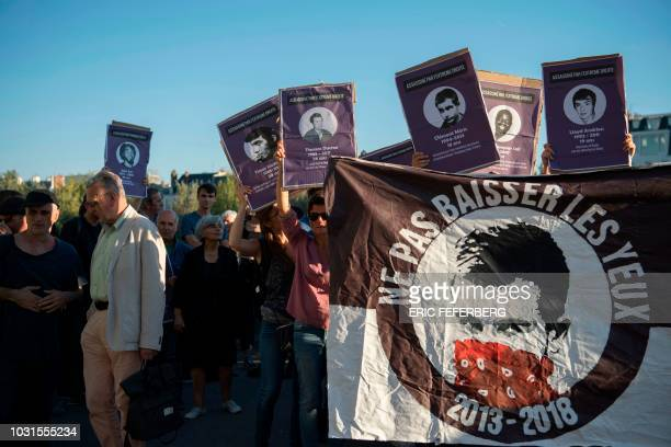 A hundred of peoople including some antifascists activists hold placards and a banner depicting Clement Meric as they gather at the Carroussel bridge...