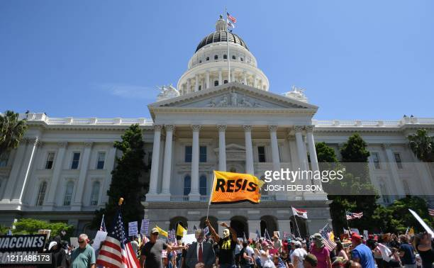 Hundreds gather to protest the shelter-in-place rules in effect amid the novel coronavirus pandemic at California's state capitol building in...