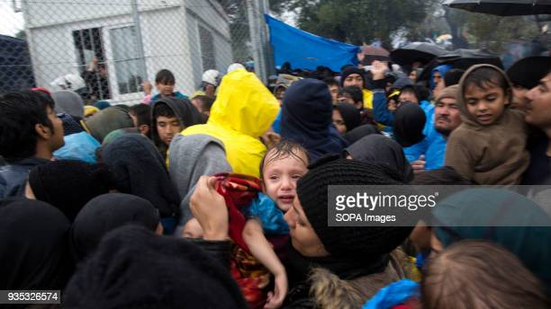 Hundreds of asylumseekers including women and children wait under cold rain to enter Moria Camp where they are required to register after arriving in...