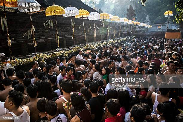 Hundreds of Balinese Hindu devotees soak theirself while other people queue during the Banyu Pinaruh ritual at Tirta Empul holy spring on October 5...