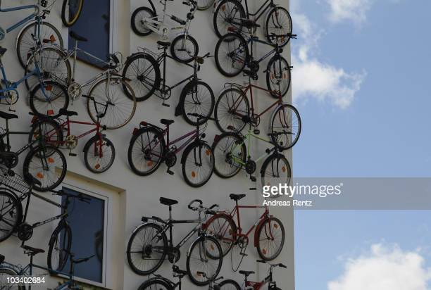 Hundreds of bicycles hang on the facade of the bike shop Fahrradhof on August 16 2010 in Altlandsberg near Berlin Germany The shop offers on his new...