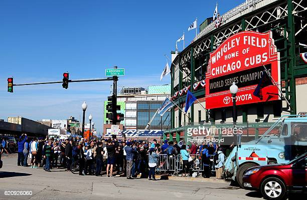 Hundreds of Chicago Cubs fans crowd under the marquee at Wrigley Field, home of the Chicago Cubs, to celebrate the Cubs' world series win against the...