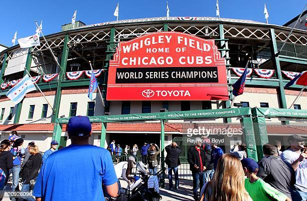 Hundreds of Chicago Cubs fans crowd under the marquee at Wrigley Field home of the Chicago Cubs to celebrate the Cubs' world series win against the...