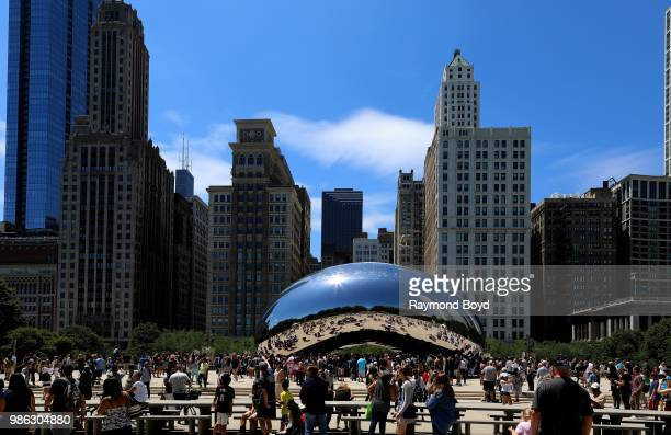 Hundreds of Chicagoans and visitors gather around Sir Anish Kapoor's 'Cloud Gate' sculpture in Millennium Park in Chicago Illinois on June 23 2018...