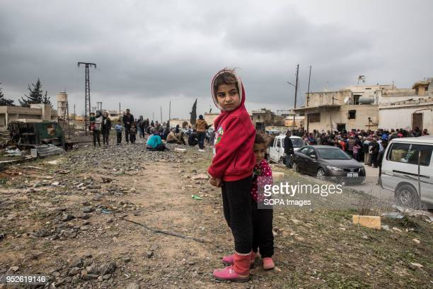 Hundreds of children reach out to aid workers distributing blankets outside of Tall Rifat An estimated 400000 refugees fleeing the twomonthold...