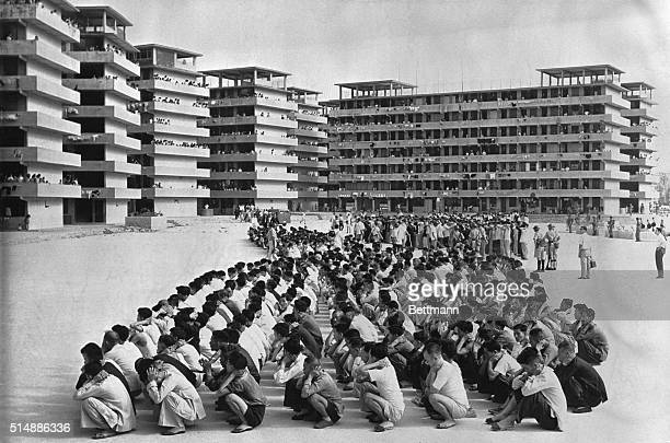 Hundreds of Chinese guarded by troops crouch with hands clasped behind their heads in the courtyard of the resettlement block in Kowloon following...