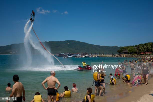 Hundreds of Chinese tourists watch the flyboard show by the beach of Hon Tam Resort on September 10 2017 in Nha Trang Vietnam With a total of 27...