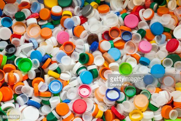 hundreds of colorful plastic bottle caps - decline stock pictures, royalty-free photos & images