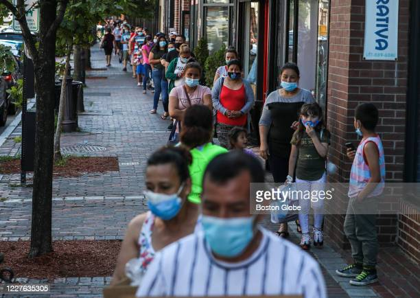 Hundreds of community members line up early to pick up food boxes at Chelsea Collaborative during their weekly food drive in Chelsea MA on July 15...