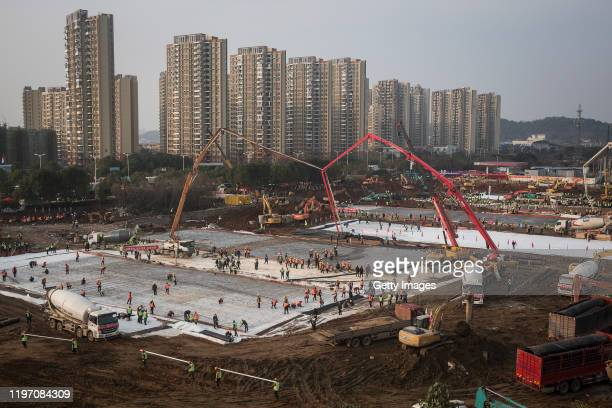 Hundreds of construction workers and heavy machinery build new hospitals to tackle the coronavirus on January 28 2020 in Wuhan China Wuhan...
