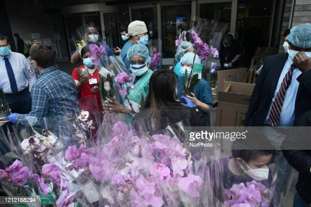 Hundreds of doctors and nurses from New York's Mount Sinai Hospital line up to receive flowers after donors delivered thousands of bouquets of...
