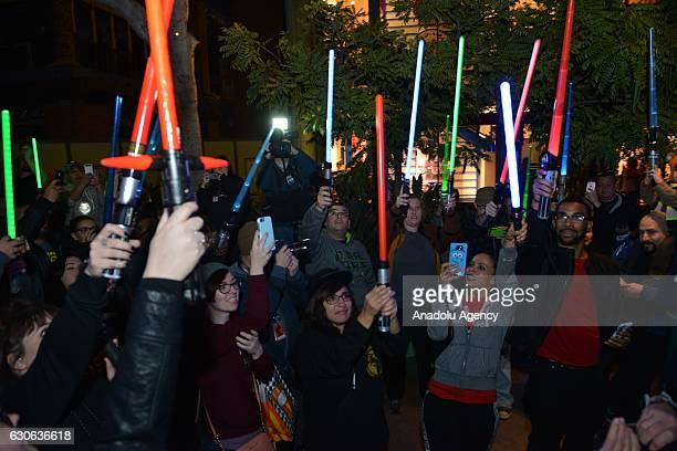 Hundreds of fans of actress and writer Carrie Fisher and her mother actress Debbie Reynolds hold lightsabers up in memory of actresses at Lightsaber...