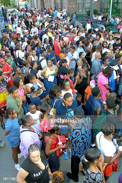 Hundreds of fans of RB singer Aaliyah wait outside the Detroit High School for Performing Arts August 27 2001 before a memorial candlelight vigil for...