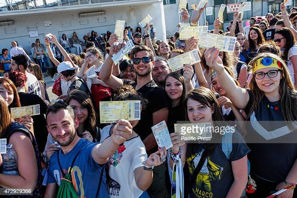 Hundreds of fans under a hot sun show tickets for the concert of Italian singer Marco Mengoni